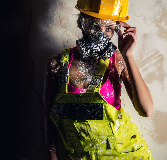 Young woman in coveralls wearing gas mask against wall