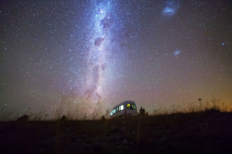 Travel Astronomy Beauty In Nature Built Structure Camper Van Field Galaxy Illuminated Land Milky Way Motor Home Nature Night No People Outdoors Scenics - Nature Sky Space Star - Space Star Field Stars Tranquil Scene Tranquility Transportation Travel Destinations
