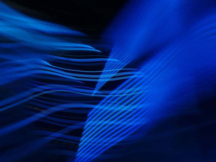 Close-up of blue light trails over black background