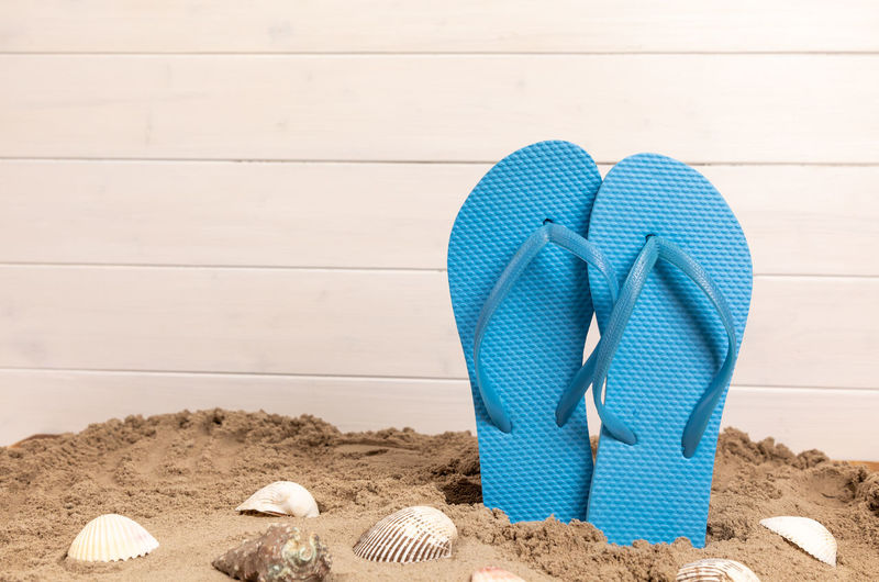 Beach Blue Container Day High Angle View Holiday Land Nature No People Pair Personal Accessory Sand Sandal Seashell Shell Shoe Slipper  Still Life Summer Trip Vacations Wood - Material