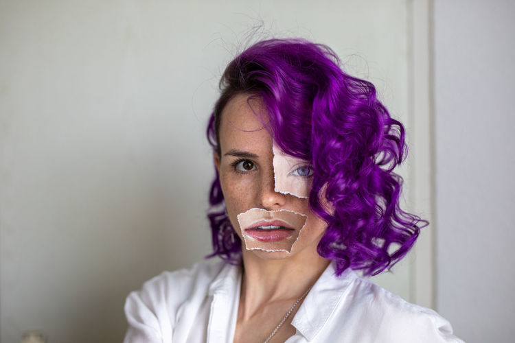 Portrait of woman wearing paper on face standing against wall at home