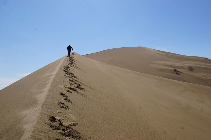 Low Angle View Of Man Walking On Sand Dune At Desert Against Clear Blue Sky