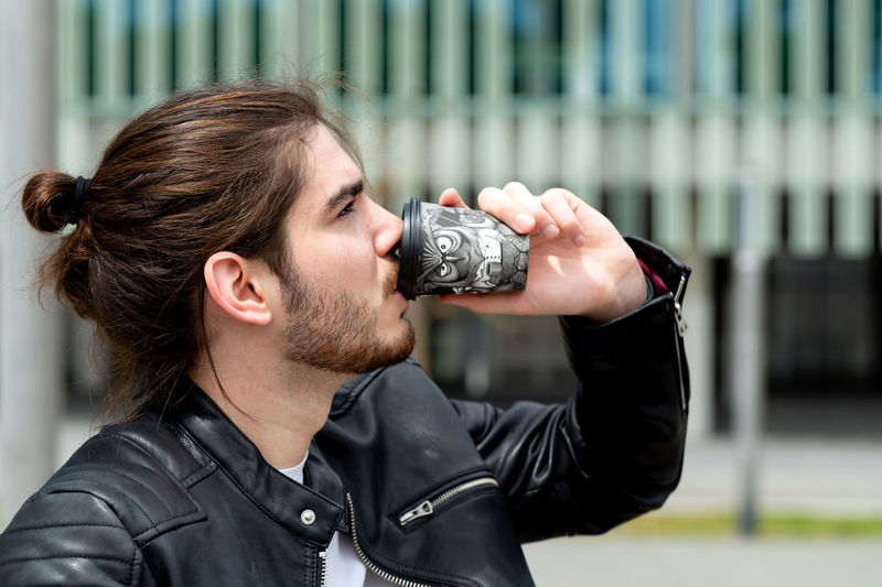 Portrait of a handsome fashionable hipster man in a black leather jacket drinking tea or coffee from a black takeaway paper cup outside. Young Adult Headshot One Person Adult Portrait Architecture Holding Black Color Activity Jacket City Focus On Foreground Young Men Occupation Brown Hair Real People Photographing Photography Themes Hairstyle Leather Jacket Leather Outdoors Coffee Coffee - Drink Coffee Cup Coffee Time Coffee Break Drinking Fashionable Handsome Model Long Hair