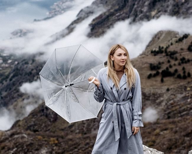 Portrait of young woman standing on rocks with umbrella
