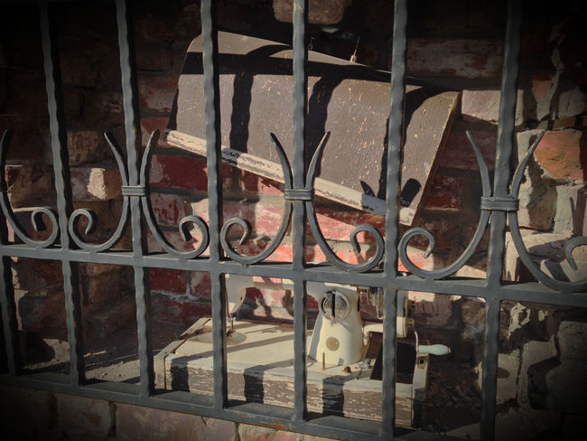Imprisoned sewing machine. Brick Wall Built Structure Iron Grate Metal No People Old Old-fashioned Outdoors Sewing Machine Still Life Streetphotography Vintage Wall - Building Feature Hidden Gems