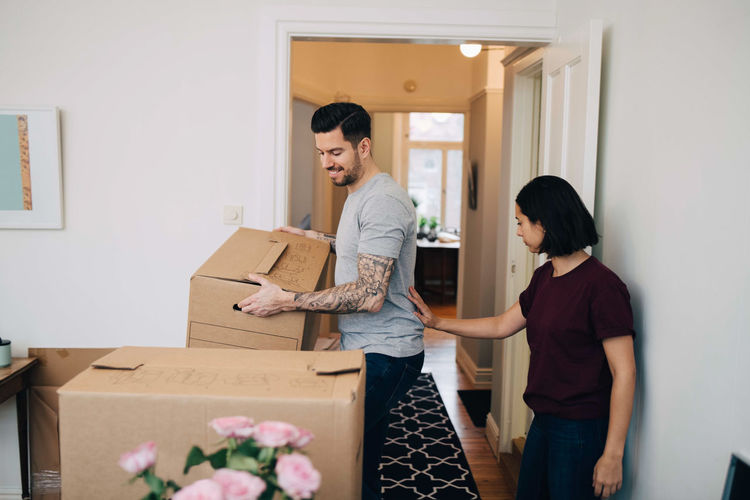 Woman standing by man carrying cardboard box in living room