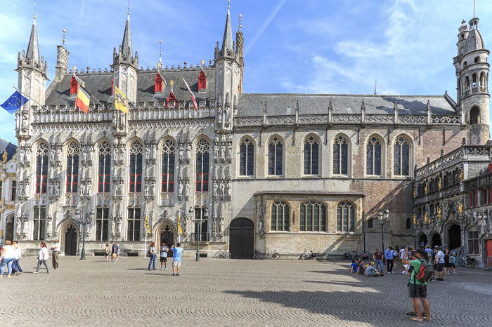 Bruges, Belgium - July 7, 2017: Tourists walking and taking pictures in front of the Provinciaal Hof in the market square in the center of Bruges, a beautiful medieval town in Belgium Beer Belgium Brugge Chocolate Dijver Canal Duvel Flanders Panoramic View Provinciaal Hof West Flanders Aerial View Belfry Tower Bikes Bruges Europe Flower French Fries Holland Market Square Medieval Town Mussels