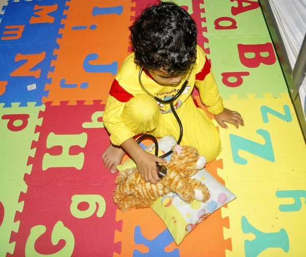 High Angle View Of Boy Playing Stuffed Toy And Stethoscope At Home