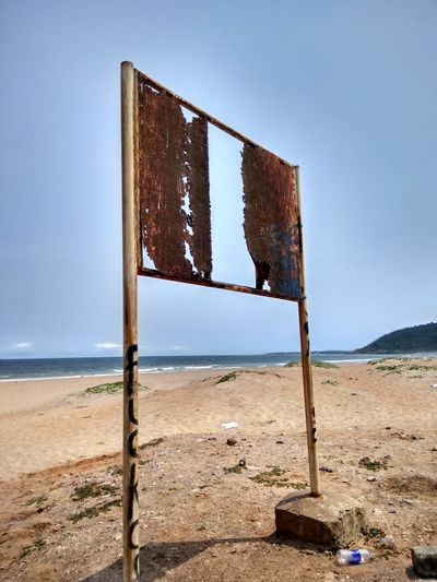 Abandoned wooden post on beach against clear blue sky