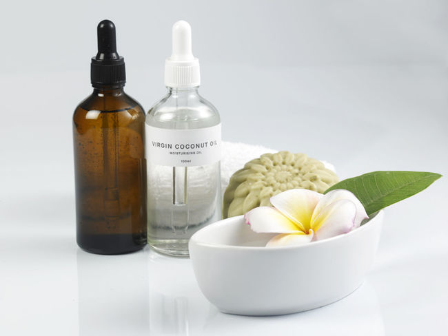 health and beauty concept bottle essential massage oil and coconut oil Health And Beauty Aromatherapy Aromatherapy Oil Body Care Bottle Close-up Coconut Oil Container Essential Oil Flower Flowering Plant Glass Container Hand Made Healthcare And Medicine Indoors  Massage Oil Nature No People Plant Relaxation Soap Still Life Studio Shot Wellbeing White Color