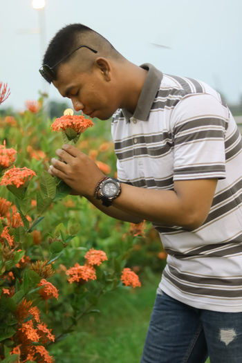 Young man smelling flower in field