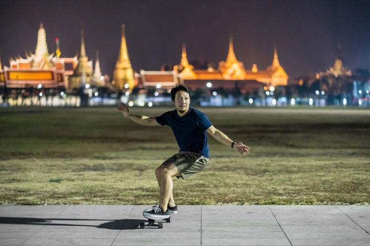 Full length of man against illuminated city at night