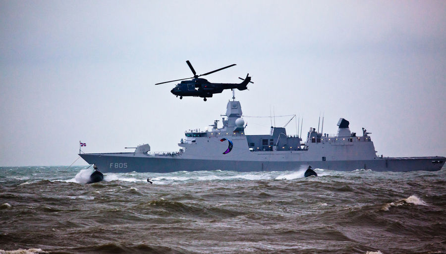 Military helicopter flying over ship at sea against sky
