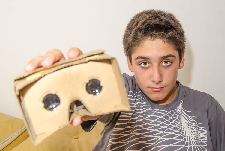 Portrait of boy showing cardboard virtual reality simulator attached to smart phone