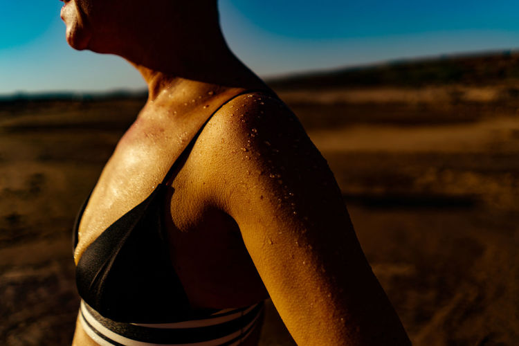 Midsection of woman sweating at land during sunny day
