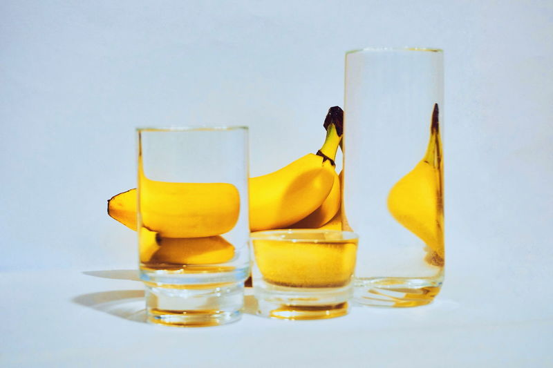 Yellow Studio Shot Indoors  Still Life Glass - Material Transparent Food And Drink Glass No People Drinking Glass Table Close-up Freshness Refreshment Healthy Eating Household Equipment White Background Food Wellbeing Blue Background Banana Illusion Water Minimalism Modern