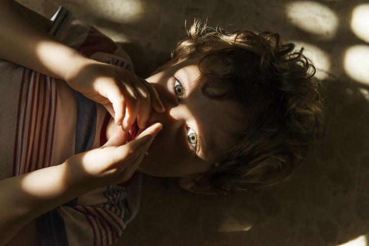 High angle portrait of boy lying on floor