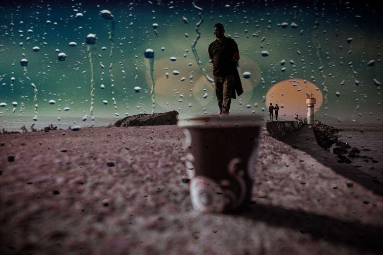 Silhouette of man standing on wet street during rainy season