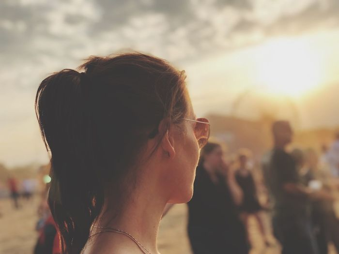 Side View Of Mid Adult Woman Wearing Sunglasses Against Sky During Sunset