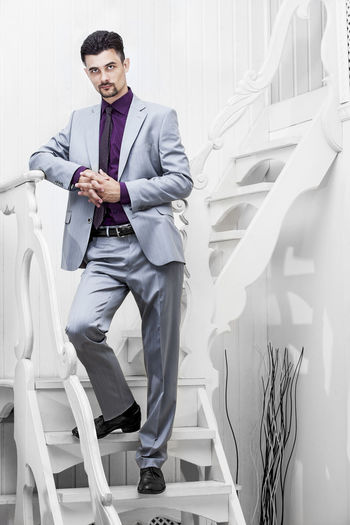 Portrait of businessman standing by steps