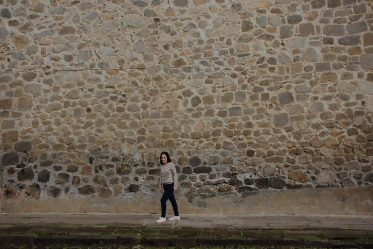 Full length of woman walking by wall