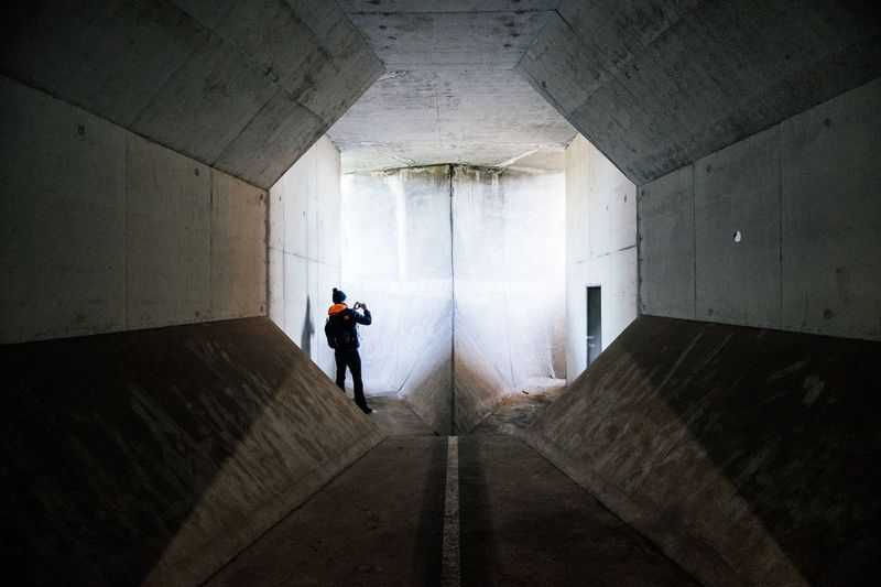 Rear View Of Man Standing In Tunnel