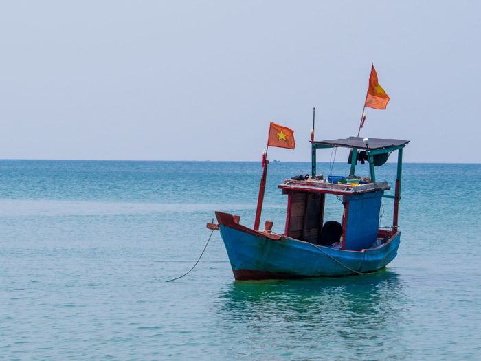 Boat moored in sea against clear sky