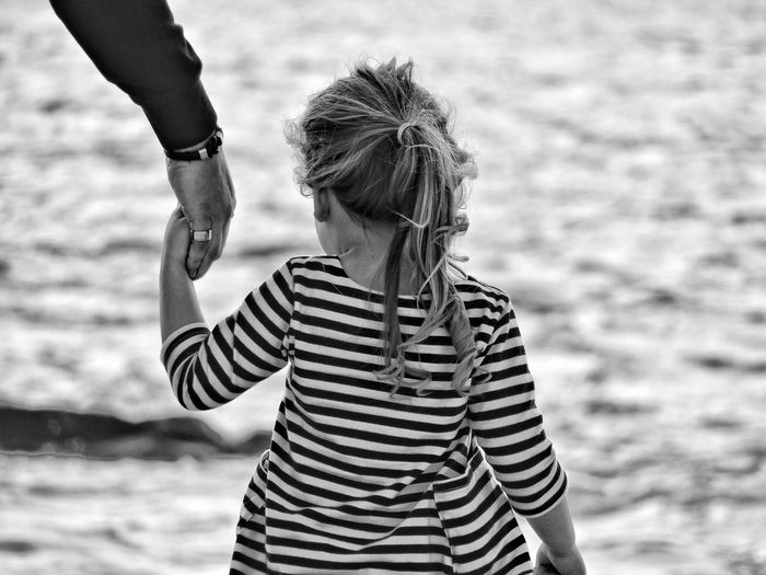 Rear view of father and daughter with holding hands at beach