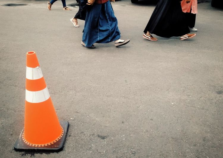 Low section of people walking by traffic cone on road