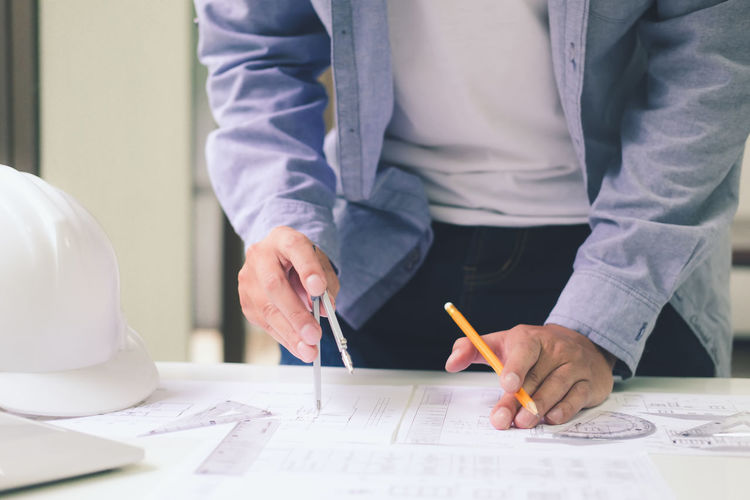 Midsection of architect working on table