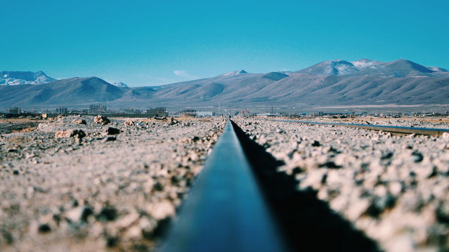 Surface level of railroad tracks against clear blue sky