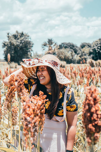 Smiling Woman Standing Amidst Flowering Plants