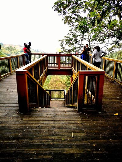 People standing on footbridge against sky