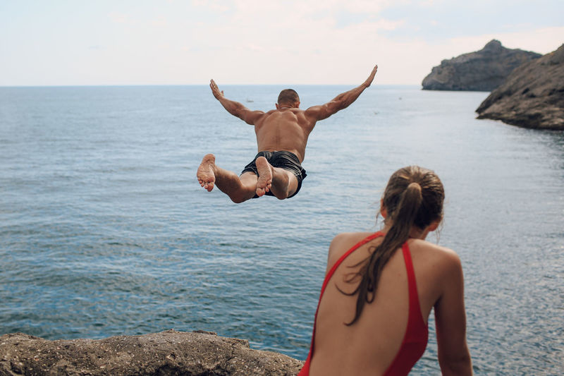 Woman looking at man diving into sea against sky