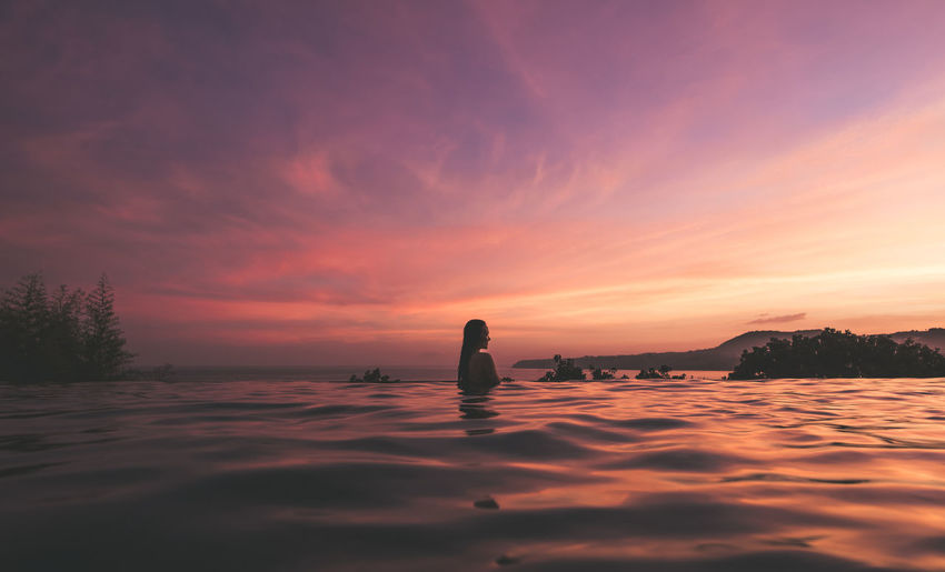 Young Woman Swimming In Infinity Pool By Sea Against Sky During Sunset