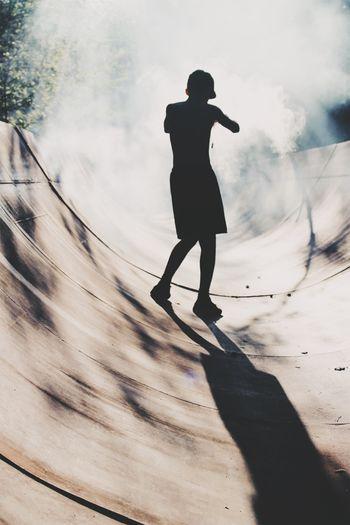 Rear View Of Silhouette Teenage Boy Standing On Skateboard Ramp