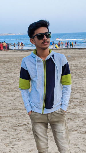 Portrait of young man wearing sunglasses standing on beach