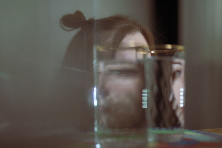 Portrait of woman seen through glass on table