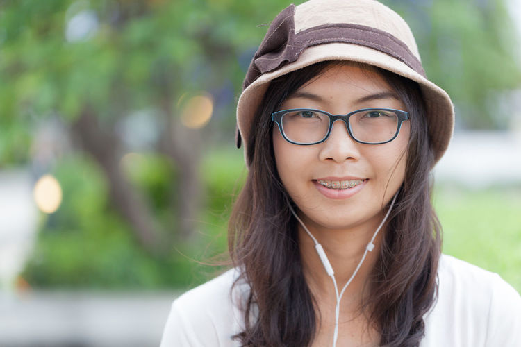 Close-up portrait of smiling young woman wearing headphones