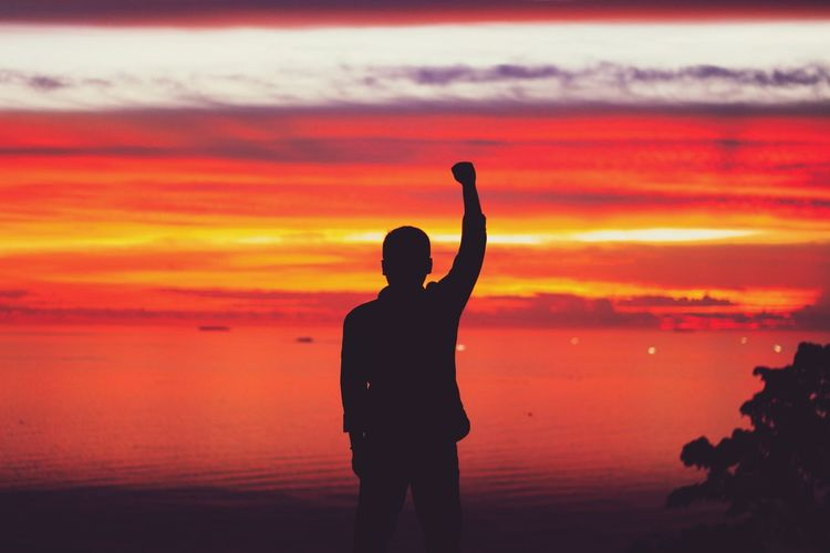 Silhouette man with hand raised standing at beach during sunset