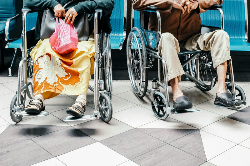 Low Section Of Men And Woman Sitting Wheel Chair At Home