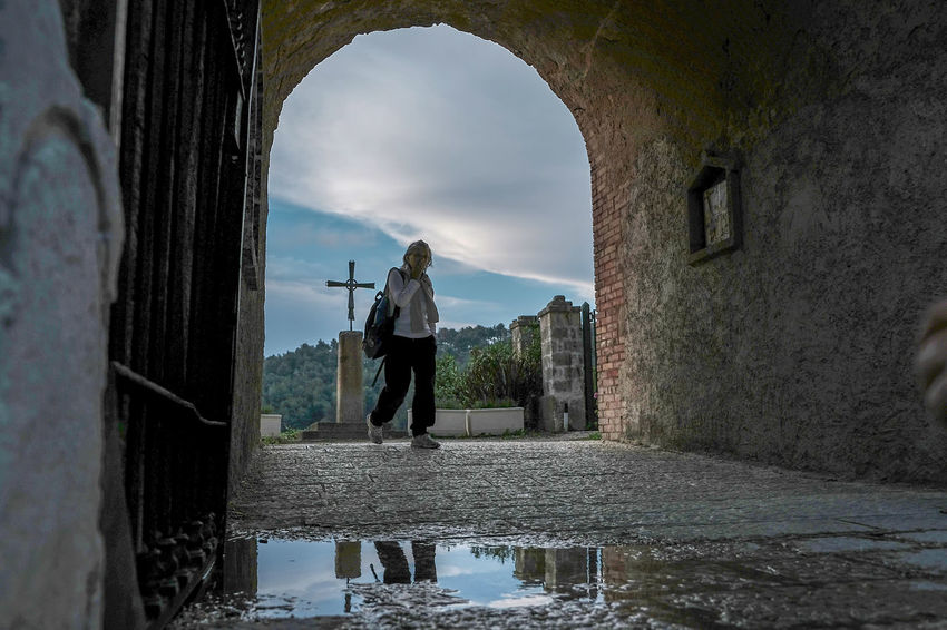Adult Arch Architecture Built Structure Day Full Length Leisure Activity Lifestyles Men Nature One Person Outdoors Real People Rear View Reflection Sky Standing Water Women