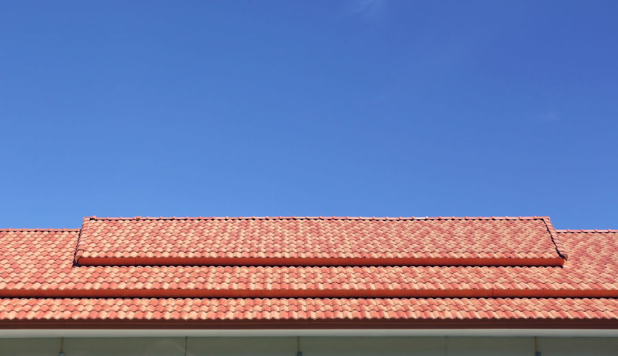Low angle view of house roof against clear sky