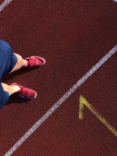 Low section of man standing on running track during sunny day