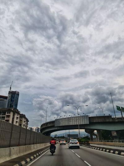 Cars on bridge against sky in city