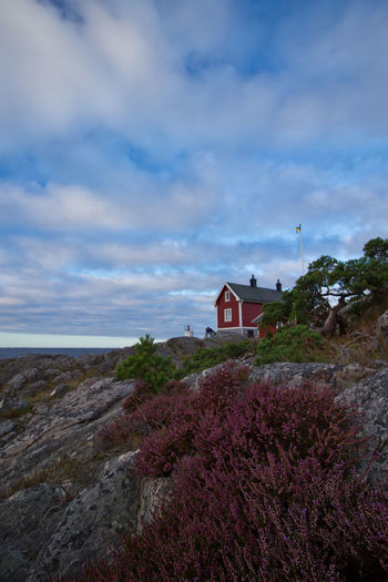 Exterior of house on rocky landscape against cloudy sky