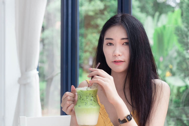Portrait of young woman holding glass window