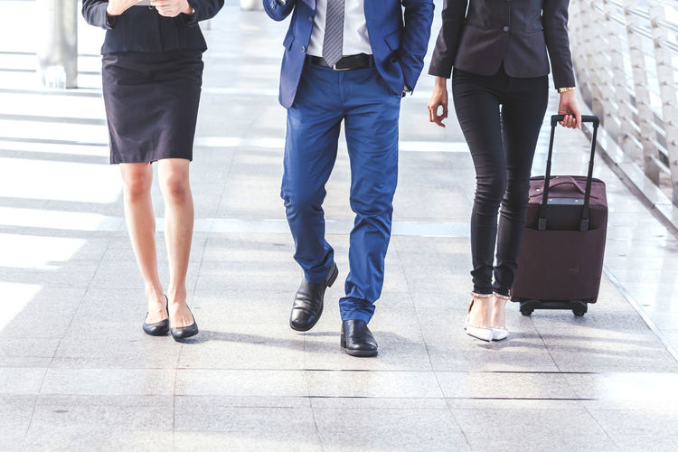 Business people walking with luggage Adult Airport Body Part Day Human Leg Lifestyles Low Section Luggage Men Motion on the move Outdoors People Real People Rear View Transportation Travel Walking Women