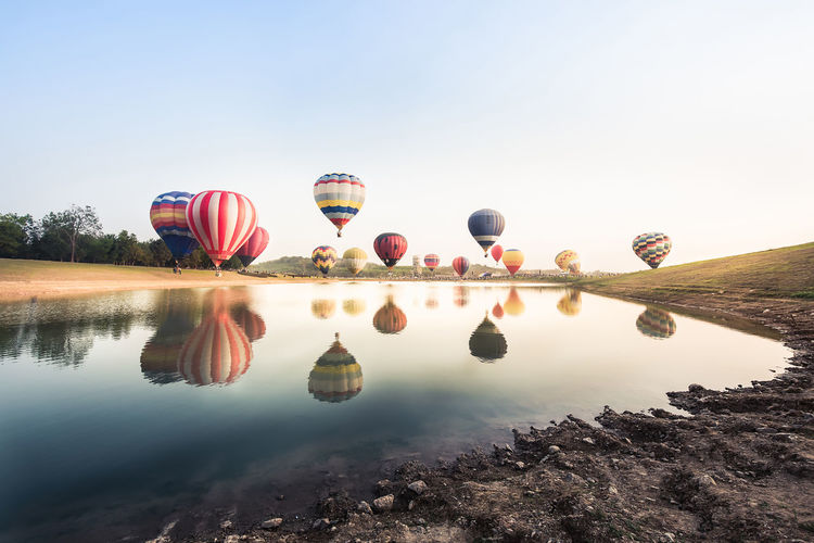 Reflection of hot air balloons in lake against clear sky