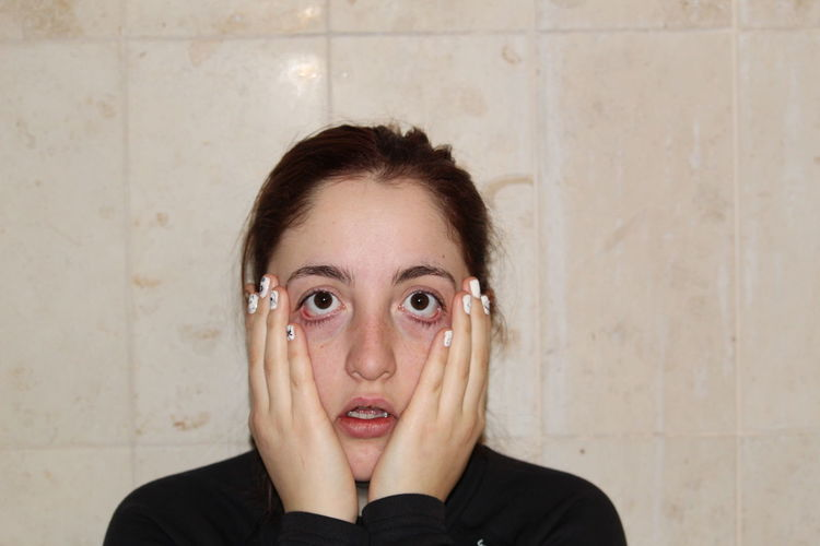 Portrait of shock young woman with hands on cheeks against wall